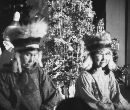 Two Native Americans sit in front of a decorated Christmas tree