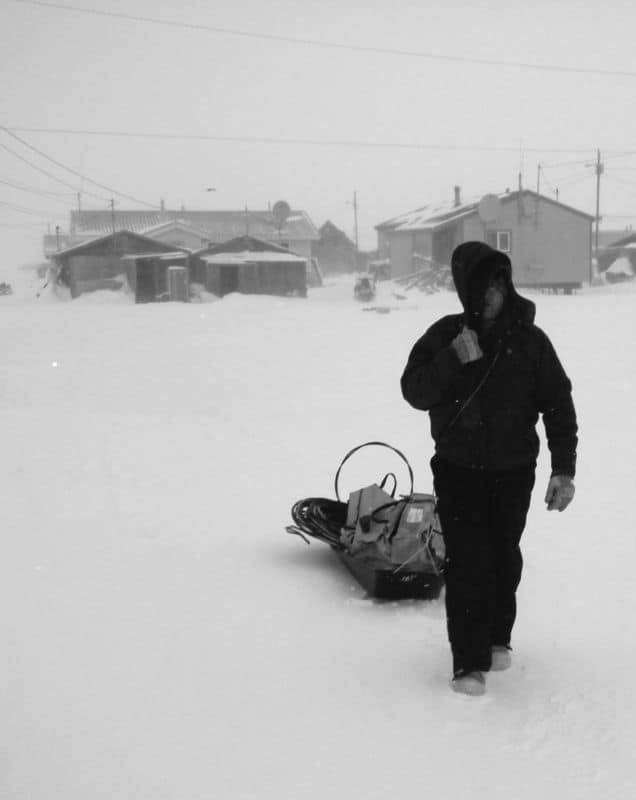 A worker drags a sled behind him.
