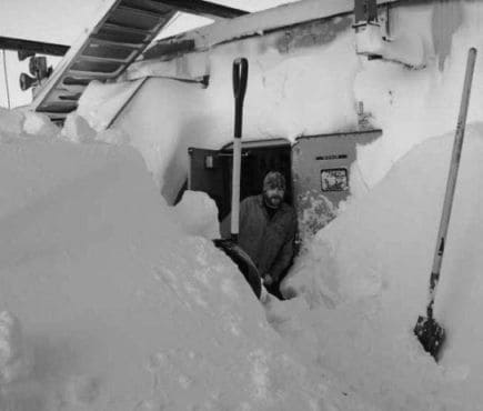 Man digging snow away from a door with a snow shovel
