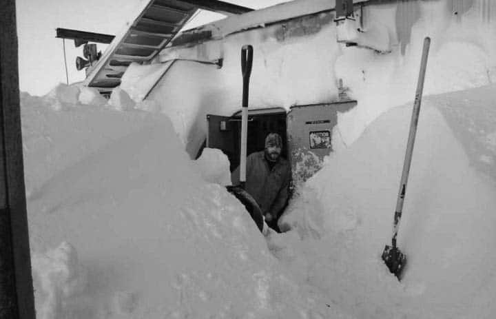 Man digging snow away from a door with a snow shovel